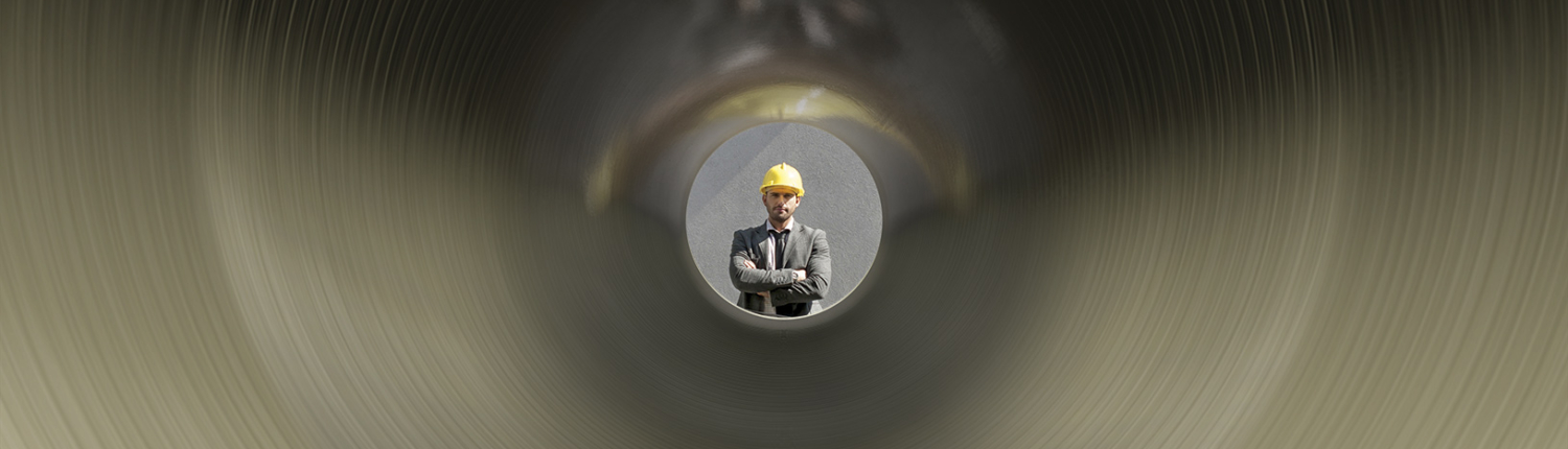 Man looks through pipe